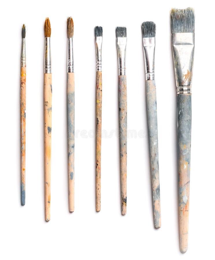 Diversos cepillos usados del arte en el fondo blanco fotografía de archivo