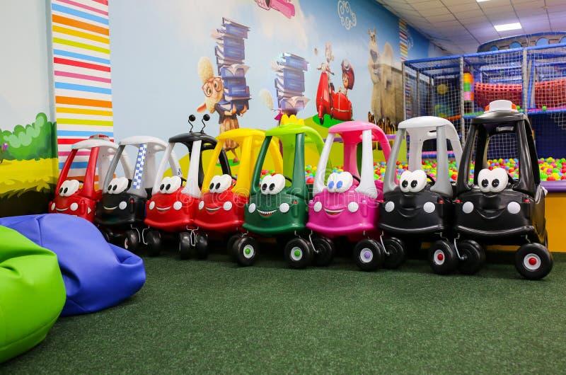 Diversos coches coloridos del juguete se están colocando en centro de entretenimiento de los niños en una línea Juegos para lo foto de archivo