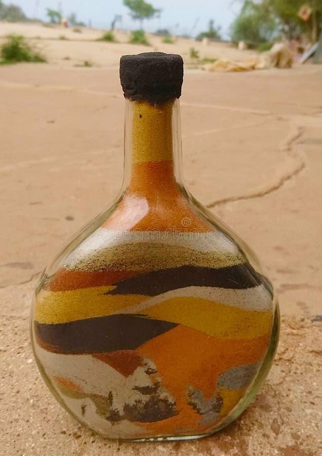 Diversos colores de la arena creaban las ilustraciones dentro de la botella fotos de archivo