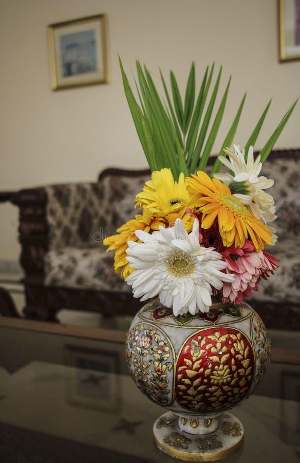 Diversos colores del Gerbera en un florero viejo del Indio-estilo en el inte imagen de archivo libre de regalías