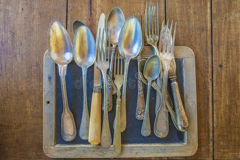 Diversos cuchillos del vintage, cucharas, bifurcaciones en la pizarra vieja fotos de archivo libres de regalías