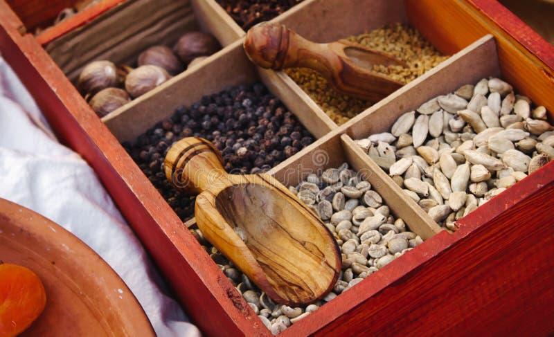 Diversos especias y condimentos exóticos en los compartimientos encajonados usados en cocinar del este con las cucharas de madera imágenes de archivo libres de regalías