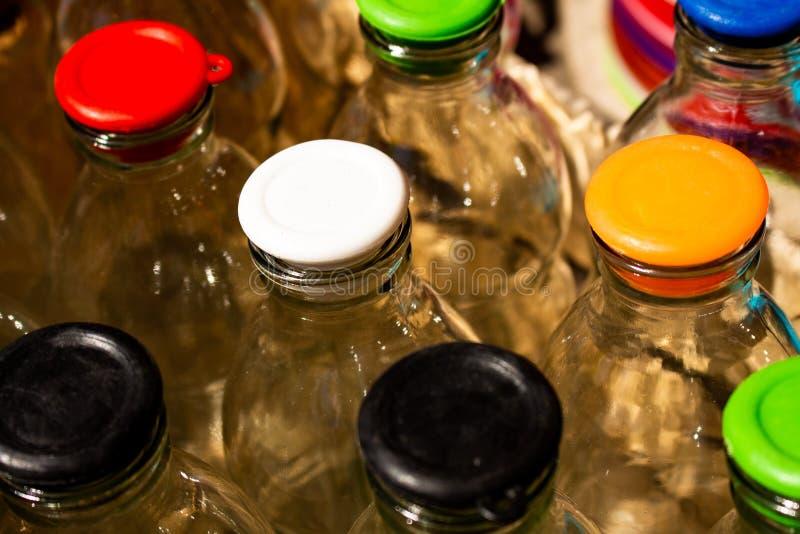 Diversos frascos de vidro transparentes com tampas coloridas foto de stock