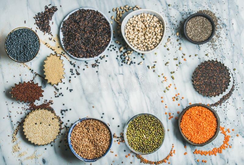 Diversos granos crudos crudos, habas, cereales en los cuencos, espacio de la copia fotografía de archivo libre de regalías