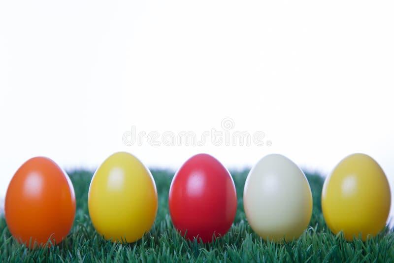 Diversos huevos de Pascua coloreados en fila con el fondo blanco imagen de archivo libre de regalías