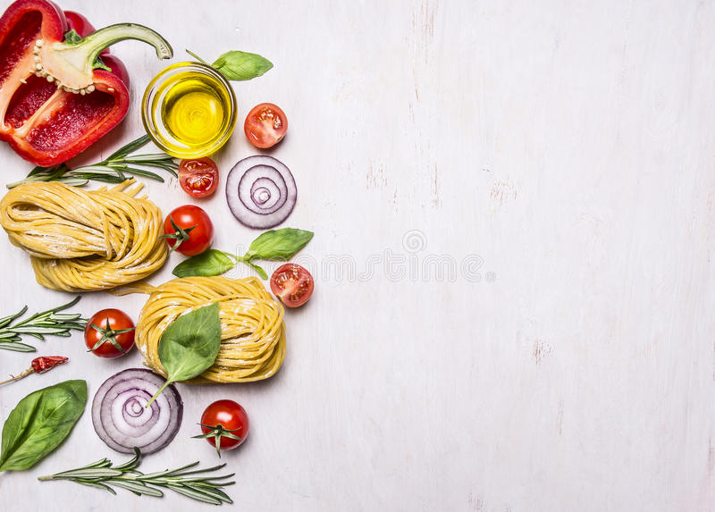 Diversos ingredientes coloridos para cocinar las pastas vegetarianas con la harina, las verduras, el aceite y las hierbas, ceboll fotografía de archivo