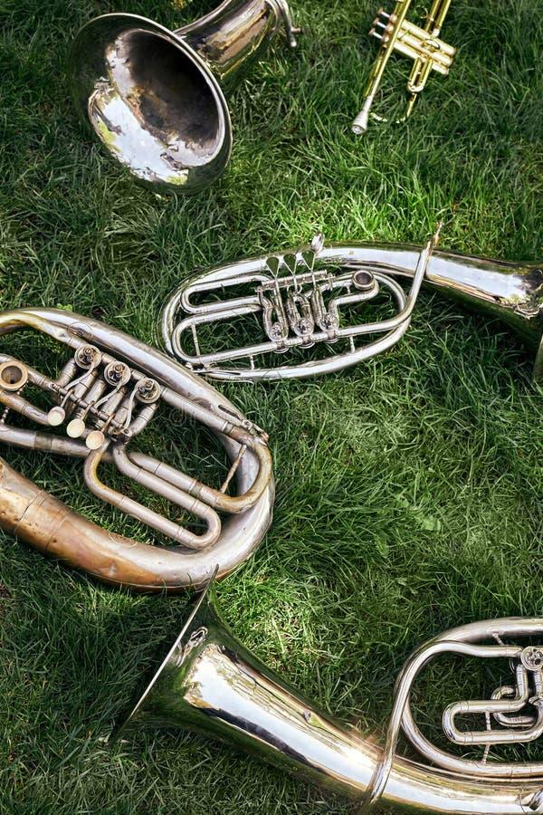 Diversos instrumentos de vento musicais antigos encontram-se na grama verde imagem de stock