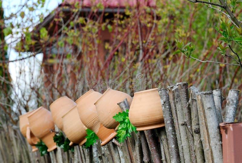 Diversos jarros da argila são colocados em uma cerca das hastes de madeira foto de stock