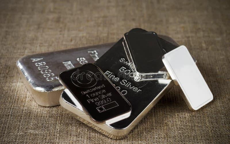 Diversos lingotes de prata diferentes na perspectiva de uma textura do pano grosseiro fotos de stock royalty free