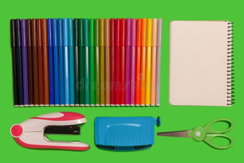 Diversos materiales de oficina en una superficie verde fotografía de archivo libre de regalías