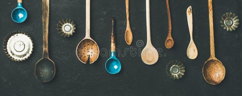 Diversos moldes de las cucharas de la cocina del vintage y de la lata de hornada, visión superior imagenes de archivo
