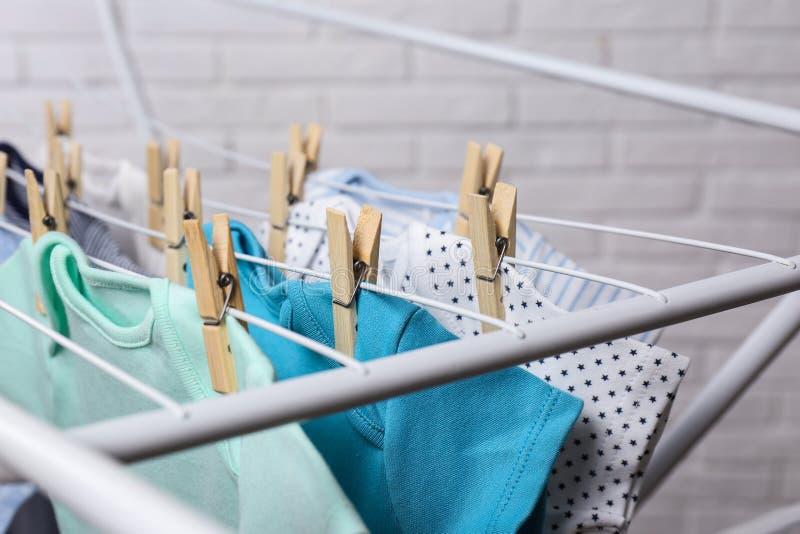 Diversos onesies lindos del bebé que cuelgan en línea de ropa cerca de la pared de ladrillo, primer lavadero imagenes de archivo