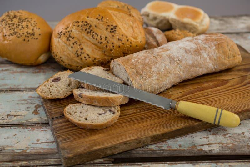 Diversos panes del pan con el cuchillo foto de archivo