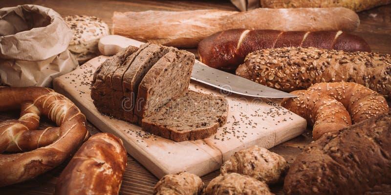 Diversos panes y rollos cocidos en la tabla de madera rústica imagen de archivo libre de regalías