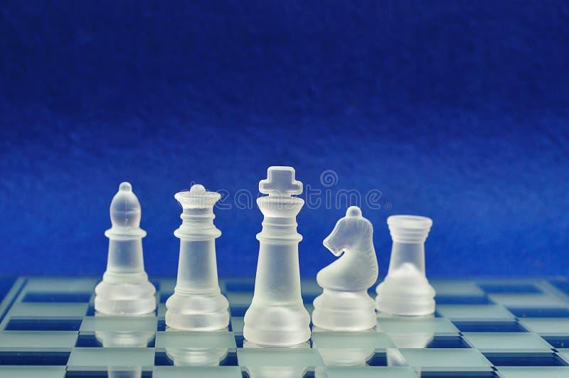 Diversos pedazos de ajedrez exhibidos en un tablero de ajedrez de cristal imagenes de archivo