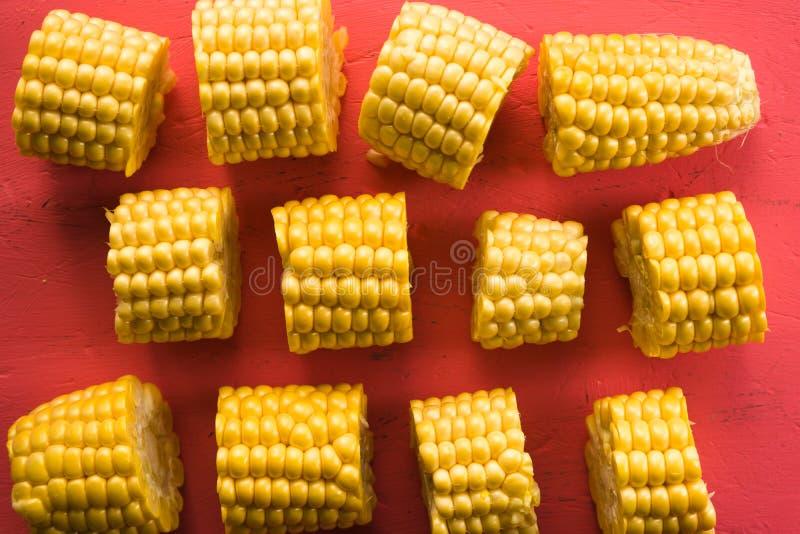 Diversos pedazos de maíz fresco en un primer rosado de la tabla imagenes de archivo