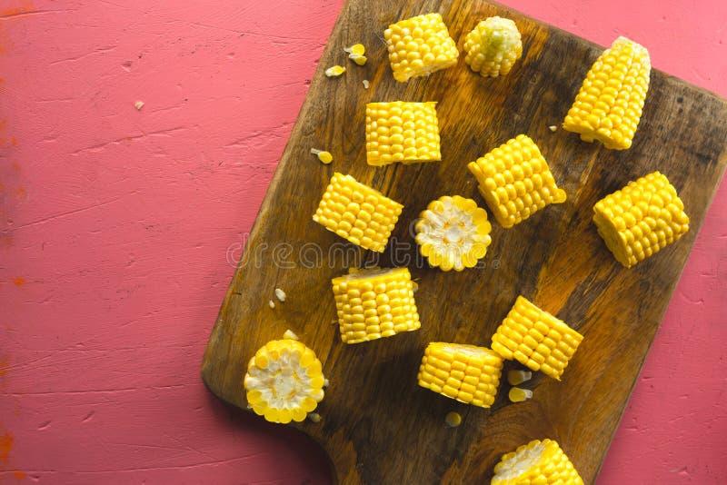 Diversos pedazos de maíz fresco en una tabla de cortar de madera foto de archivo
