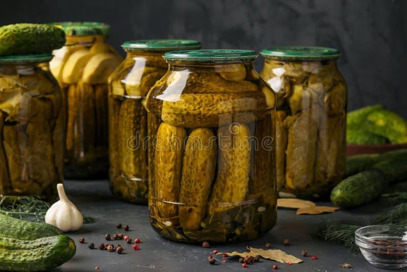 Diversos pepinos conservados en vinagre con las hojas del calabacín, del ajo y de la uva en los tarros en un fondo oscuro, foto h fotografía de archivo libre de regalías