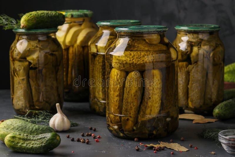 Diversos pepinos conservados en vinagre con las hojas del calabacín, del ajo y de la uva en los tarros en un fondo oscuro, foto h fotografía de archivo