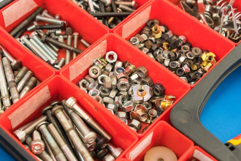 Diversos pernos de tornillos de las nueces y otras piezas clasificados en caja imagenes de archivo