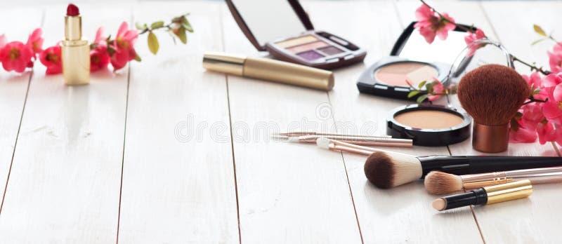 Diversos productos cosméticos para el maquillaje con las flores rosadas en un fondo de madera blanco con el espacio de la copia fotos de archivo