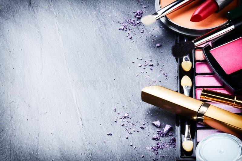 Diversos productos de maquillaje en fondo oscuro foto de archivo