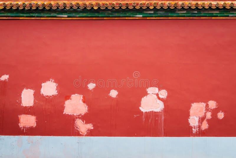 Diversos remendos na parede de tijolo pintada vermelha fotografia de stock royalty free