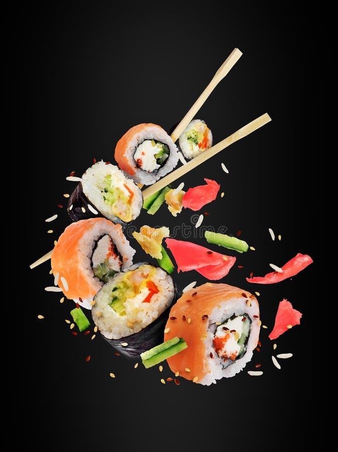 Diversos rollos de sushi frescos con los palillos congelados en el aire imagen de archivo