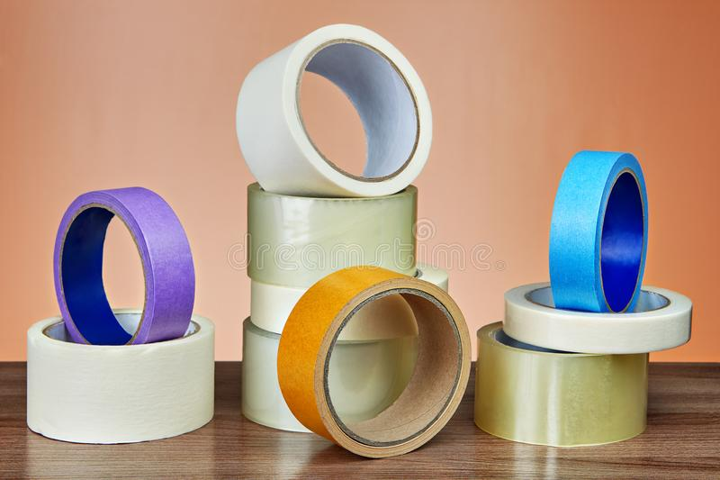 Diversos rolos da fita adesiva para fins diferentes na tabela fotografia de stock royalty free