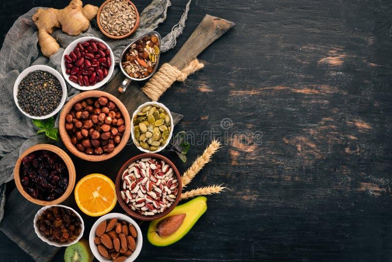Diversos superfoods Frutas secadas, nueces, habas, frutas y verduras En un fondo de madera negro imagen de archivo libre de regalías