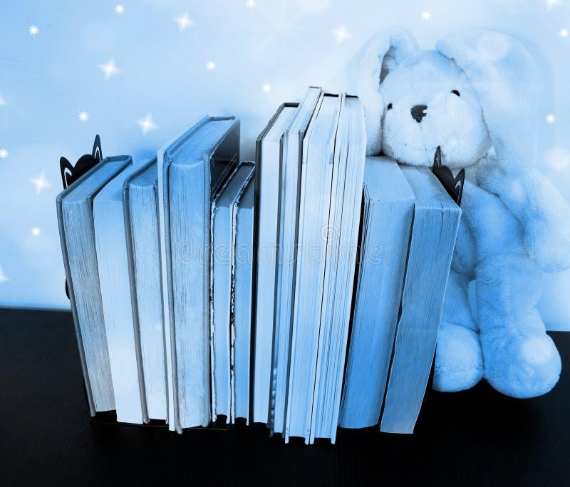 Diversos suportes de livros entre extremidades de livro Um brinquedo do luxuoso está ao lado dos livros foto de stock royalty free
