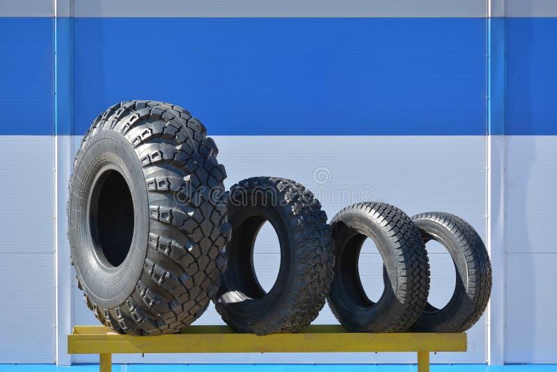 Diversos tamaños de los neumáticos para los coches en el soporte foto de archivo libre de regalías