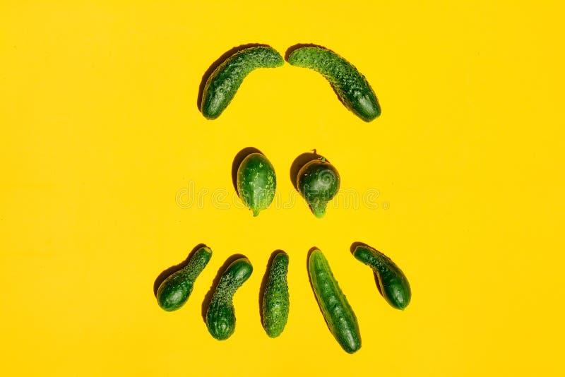 Diversos tamaños y los pepinos de las formas en un fondo amarillo forman una cara sonriente foto de archivo