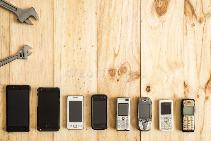 Diversos telefones celulares velhos e novos com chaves inglesas de aço imagens de stock