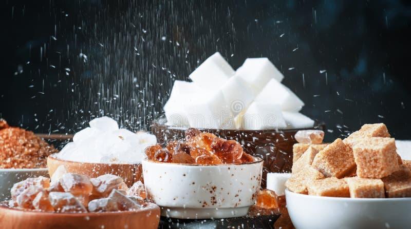 Diversos tipos clasificados de azúcar en cuencos en una tabla en una oscuridad foto de archivo libre de regalías