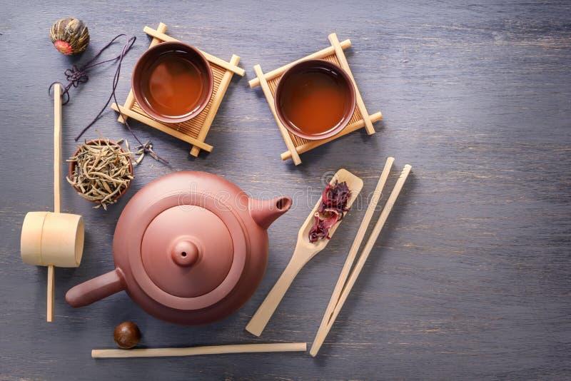 Diversos tipos de atributos do chá verde, do chá preto, do chá do hibiscus e da cerimônia de chá - um bule cerâmico, copos, um fi imagem de stock