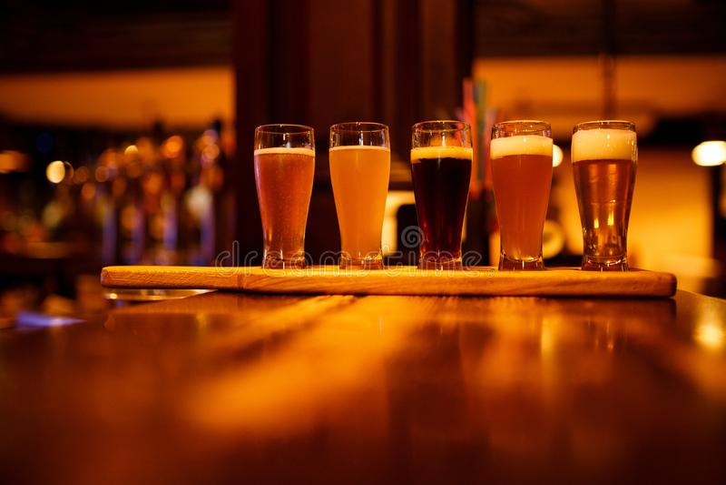 Diversos tipos de cerveza del arte en pequeños vidrios en una tabla de madera en un pub fotografía de archivo