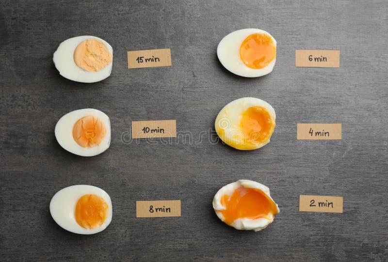 Diversos tipos de huevos hervidos en fondo gris foto de archivo