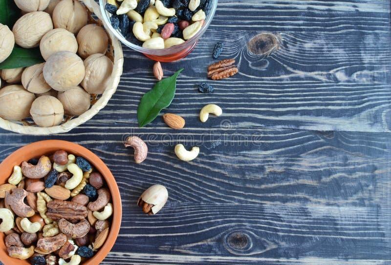 Diversos tipos de nueces y de pasas en los oligoelementos útiles nuts de un fondo de madera imagen de archivo libre de regalías