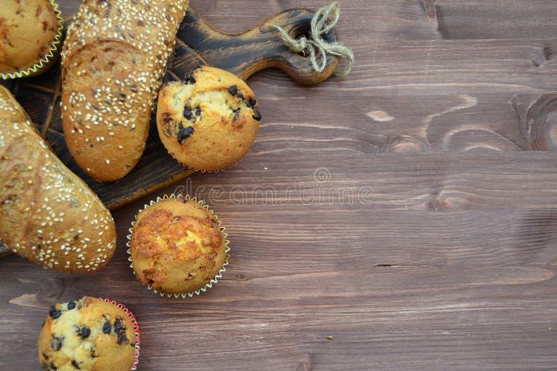 Diversos tipos de pan: blanco y negro con las semillas, los baguettes y las magdalenas con el espacio de la copia conceptual fotos de archivo libres de regalías