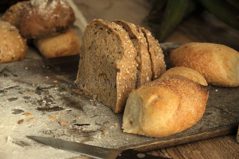 Diversos tipos de pan cocido en una tabla oscura de la frente Pan en un fondo marrón en la tabla foto de archivo libre de regalías