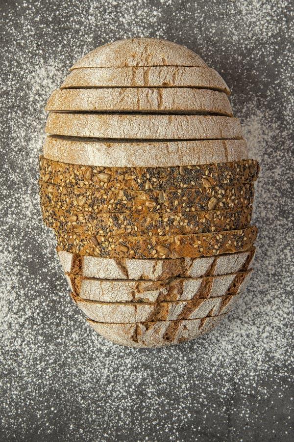 Diversos tipos de pan cortados en un fondo oscuro asperjado con la harina imagen de archivo
