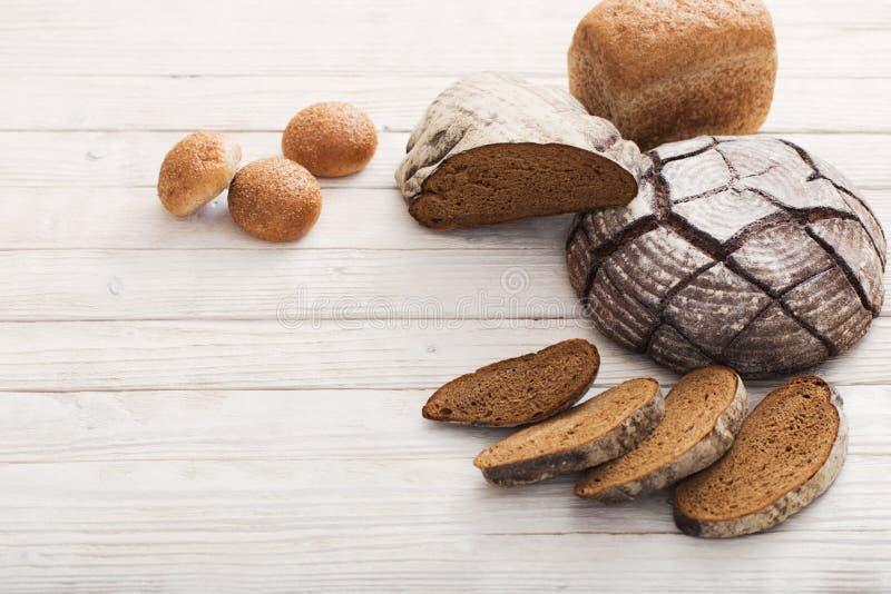 Diversos tipos de pan en fondo de madera imagenes de archivo