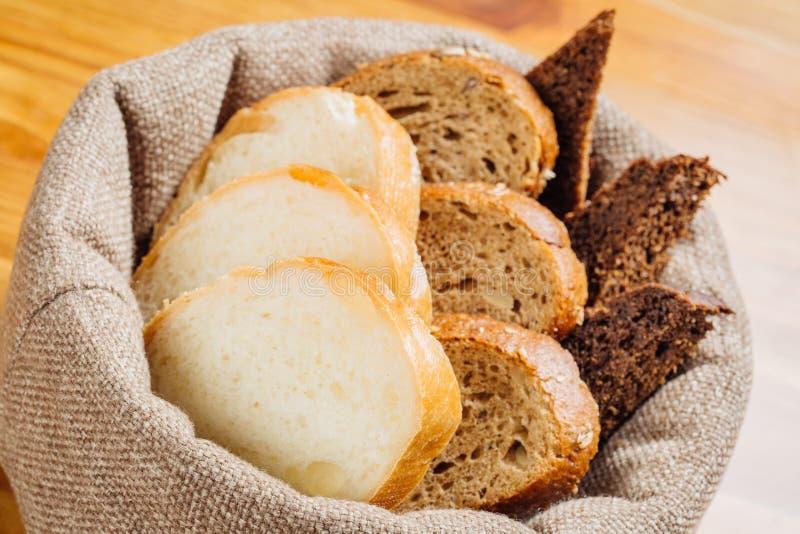 Diversos tipos de pan en la cesta en la tabla imagen de archivo libre de regalías