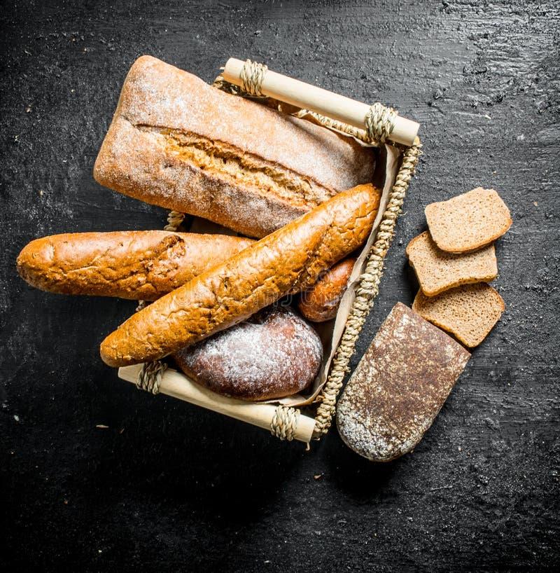 Diversos tipos de pan en la cesta imagen de archivo