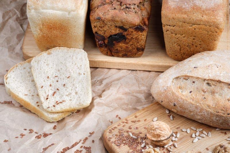 Diversos tipos de pan de la panadería, mentira en un tablero de madera del roble Alrededor de las nueces y de las avellanas foto de archivo libre de regalías