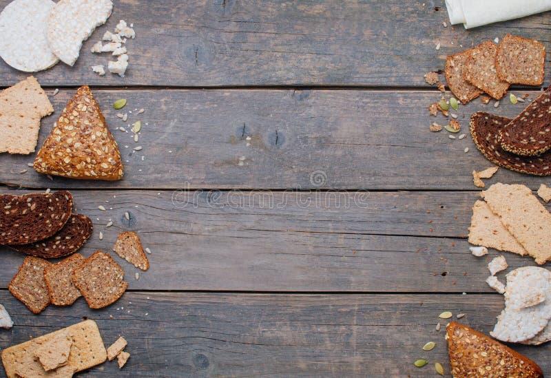 Diversos tipos de pan y de biscotes curruscantes en fondo de madera con el espacio de la copia fotografía de archivo