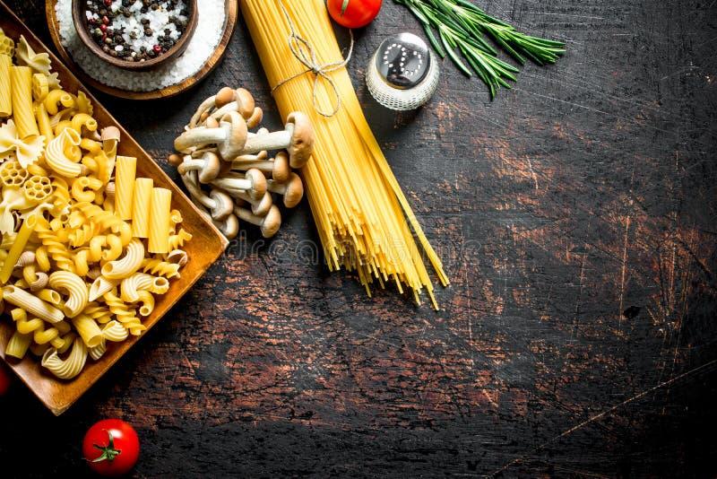 Diversos tipos de pastas crudas con los tomates, las especias y las setas imagenes de archivo