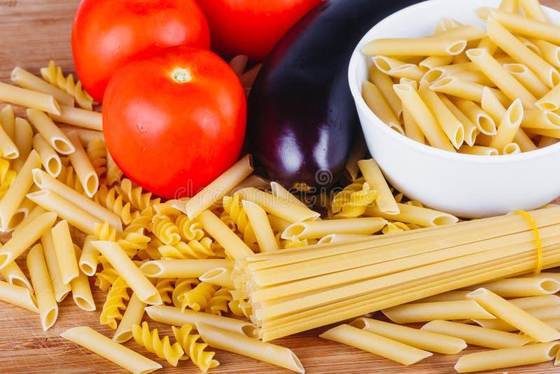 Diversos tipos de pastas italianas crudas con los tomates y otras verduras, fondo de la visión superior Foco seleccionado fotos de archivo