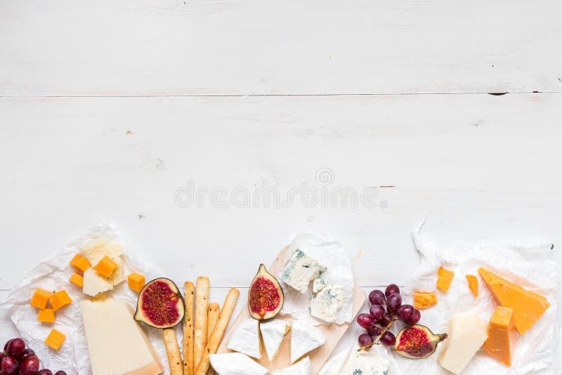 Diversos tipos de queso con las frutas en la tabla blanca de madera con el espacio de la copia Visión superior imagen de archivo libre de regalías